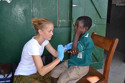 Wolontariuszka pomaga lokalnemu dziecku w Ghanie