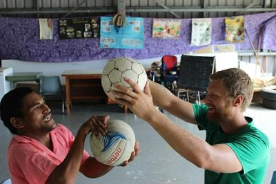 A recent graduate works with a patient at his physical therapy internship in Samoa.