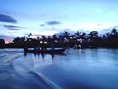 A scenic photograph of a boat on a lake at sunset in Fiji