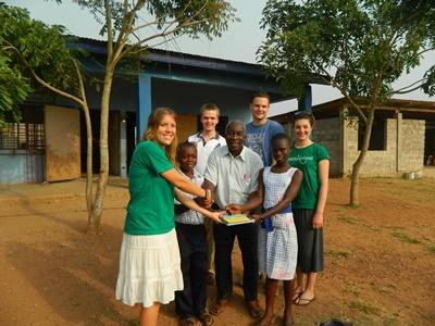 Projects Abroad volunteers donate books upon introduction to local staff member at a school in Ghana
