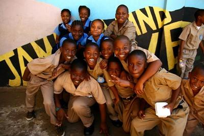 Local school children in Jamaica pose for a picture outside of their volunteer project placement
