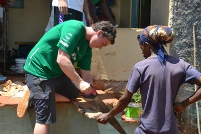 A Jamaican builder works alongside a Projects Abroad volunteer