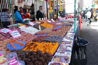 A stall at a street market in Mexico selling baked goods and sweets.