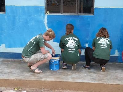 A group of volunteers help with painting at a Dirty Day in Tanzania.