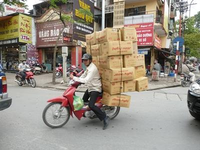 Local Vietnamese man carries boxes on the back of his motorbike
