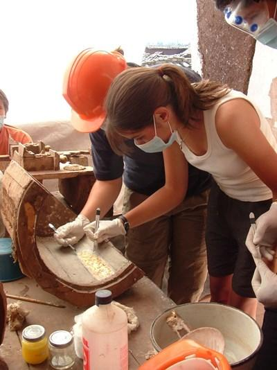 Volunteers on an Archaeology Project inspect an artifact found in their dig overseas