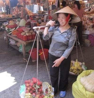 Local woman in a market wears a straw hat in Vietnam
