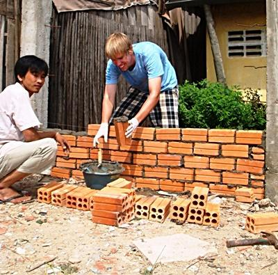 Volunteer constructing a building on a Community Building Project