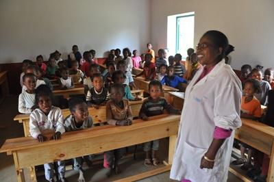 A local teacher stands in front of her class in Madagascar, Africa