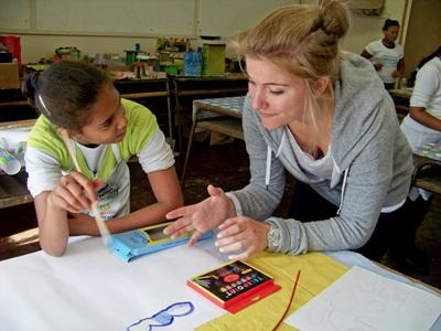 A student and volunteer teacher talk during class at a school in Cape Town, South Africa