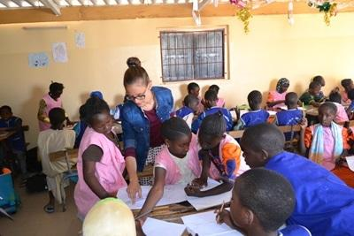 Senegalese children get help from a volunteer teacher at their school