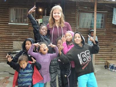A group of children spend time with a female volunteer in a South African township