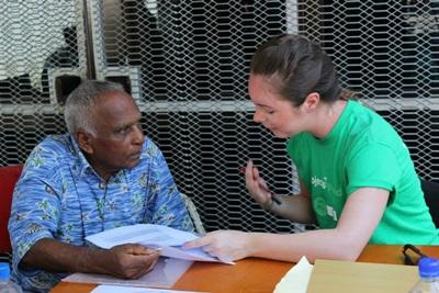 A Fijian man listens to a Projects Abroad Nutrition intern at an outreach