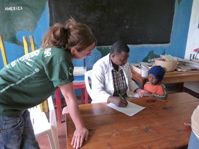 A Tanzanian occupational therapist works with a local child in Dar es Salaam while a Projects Abroad intern observes