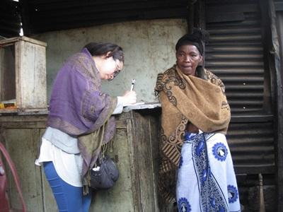 Volunteer on the Microfinance project interviews local woman to understand international development in Tanzania