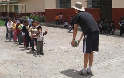 A group of Peruvian children enjoy an outdoor activity with a volunteer