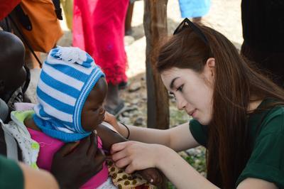 Wolontariuszka z projektu Farmacji bada lokalną dziewczynkę.