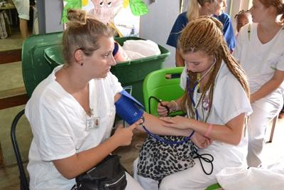 A medical volunteer conducts a blood pressure check for a woman at a community outreach