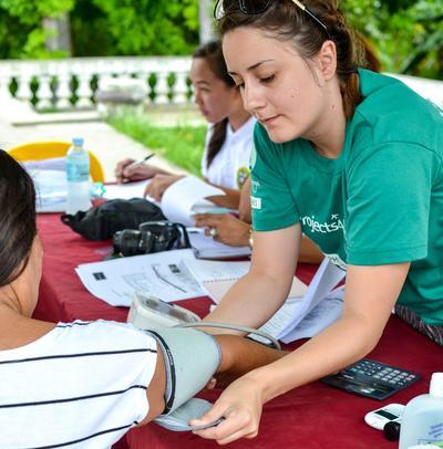 Wolontariusza Projects Abroad sprawdza ciśnienie krwi pacjentce