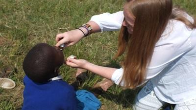 A medical volunteer helps a child with his injury in Kenya