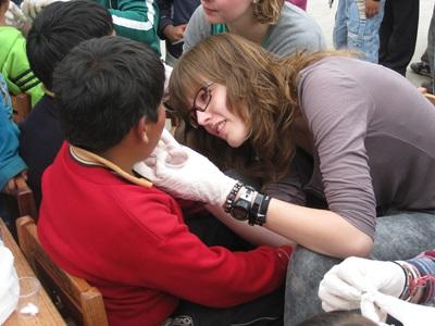 A female volunteer promotes dental hygiene at an outreach in Peru