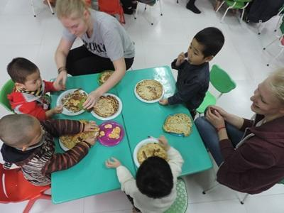 Vietnamese children enjoy their meal with two Care volunteers.