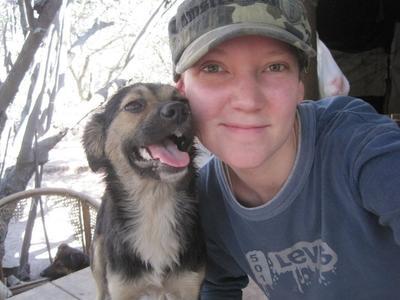Wolontariuszka uśmiecha się wraz z uradowanym psem, Argentyna