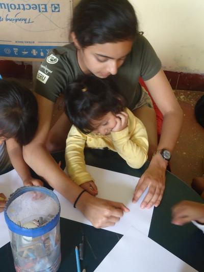 Wolontariuszka pokazuje dzieciom, jak rysować