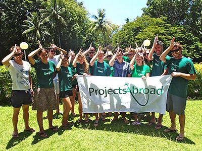 Shark Conservation volunteers  hold the projects abroad flag at their placement in Fiji